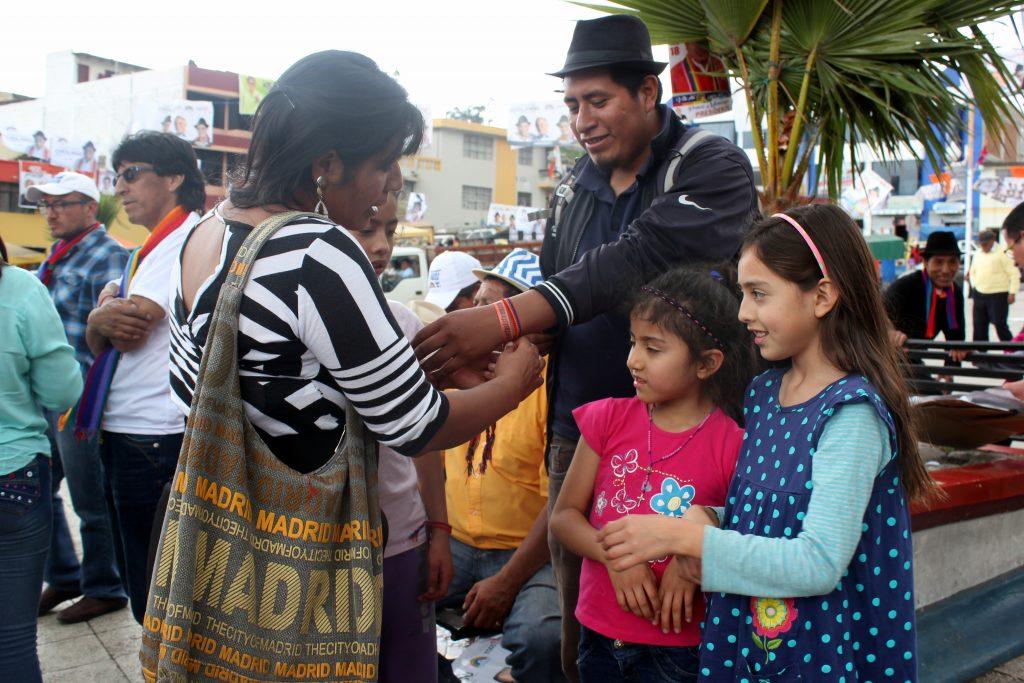 Idag engagerar sig Esther i Conaies egna parti Pachakutik. Inför den politiska kampanjen trär hon regnbågsfärgade armband på bekanta och charmar till sig deras röster i valet. Foto Elli Viljanen.