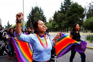 Katy Betancourt, ansvarig för kvinnofrågor inom urfolksnätverket Conaie i Ecuador, går med urfolkens flagga vid en demonstration under den internationella dagen mot våld mot kvinnor. Foto Hanna Rissler.